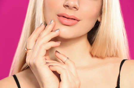 Beautiful young woman with shiny manicure on color background, closeup. Nail polish trends