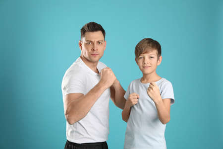 Portrait of sporty dad and his son on color background