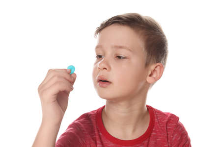 Little child taking pill on white background. Danger of medicament intoxication