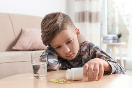 Little child with pills and water at table indoors. Danger of medicament intoxication Фото со стока