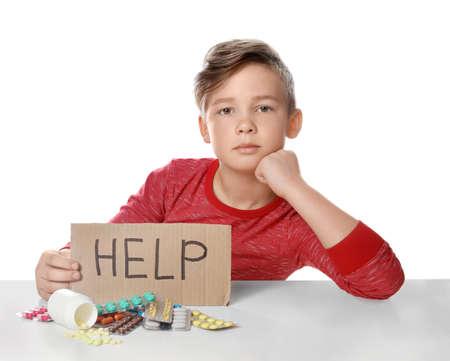 Piccolo bambino con molte pillole diverse e aiuto di parole scritte su cartone su sfondo bianco. Pericolo di intossicazione da farmaci