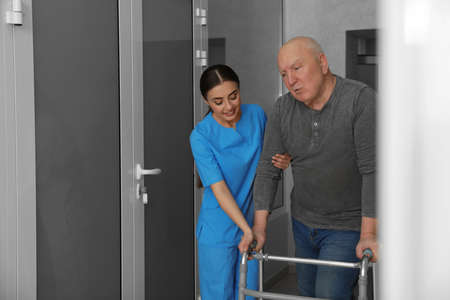 Nurse assisting senior patient with walker in hospital hallway