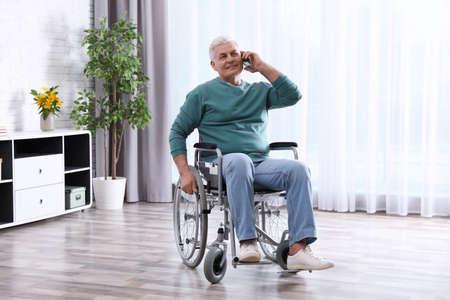 Senior man in wheelchair talking on phone at home