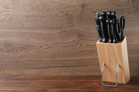 Holder with set of knives on wooden table. Space for text