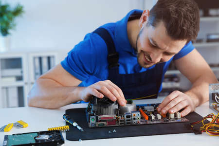 Male technician repairing motherboard at table indoors