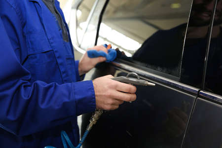 Worker cleaning automobile with gun and rag at car wash, closeup Foto de archivo - 124648611