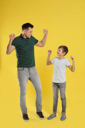 Portrait of emotional dad and his son on color background Фото со стока