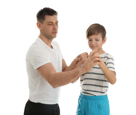 Dad teaching his son to fight isolated on white