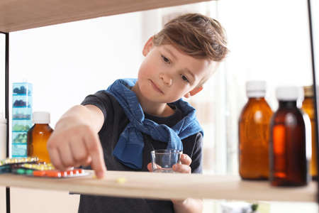 Little child taking pills from shelf at home. Danger of medicament intoxication