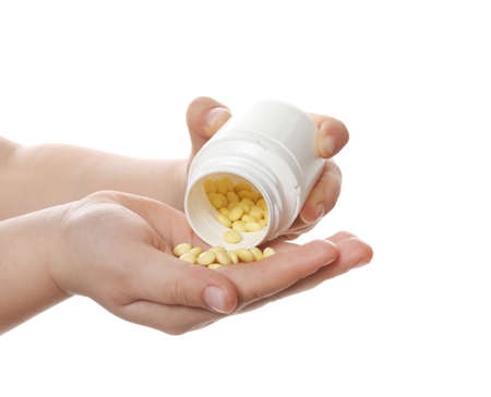 Little child with pills on white background, closeup. Danger of medicament intoxication