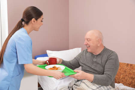 Nurse giving tray with food to senior patient in hospital ward. Medical assisting