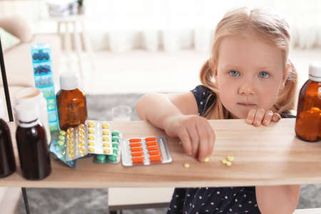 Little child taking pills from shelf at home. Danger of medicament intoxication Reklamní fotografie