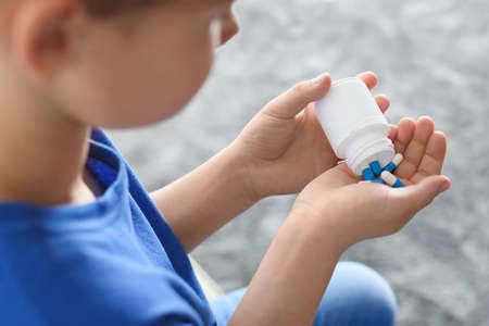 Piccolo bambino con le pillole a casa, primo piano. Pericolo di intossicazione da farmaci