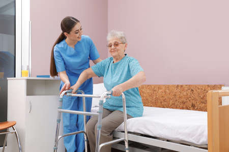Nurse assisting senior woman with walker to get up from bed in hospital ward