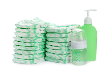 Stacks of diapers and baby accessories on white background