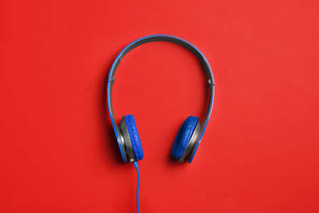 Stylish headphones on color background, top view
