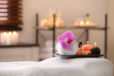 Composition with towel, candles and oils on massage table in spa salon. Space for text