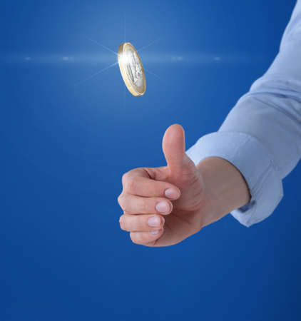 Young man throwing coin on blue background, closeup. Space for text Banque d'images - 124654730