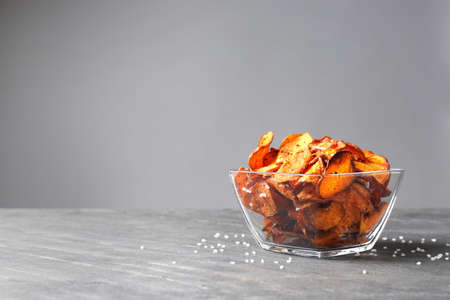 Bowl of sweet potato chips and salt on table against grey background. Space for text