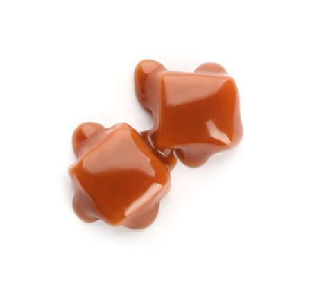 Delicious candies with caramel sauce on white background, top view