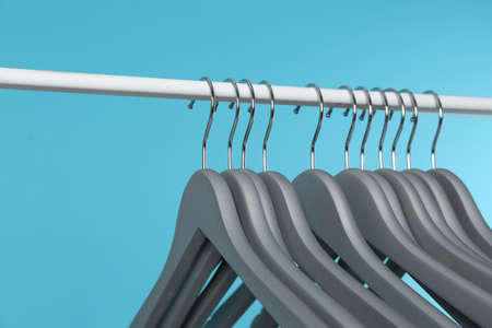 Metal rack with clothes hangers on color background, closeup