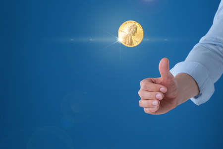 Young man throwing coin on blue background, closeup. Space for text Banque d'images - 124655363
