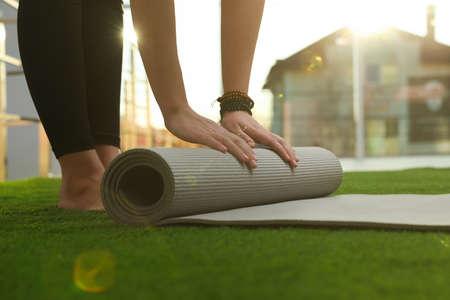 Young woman rolling yoga mat in sunlit room, closeup