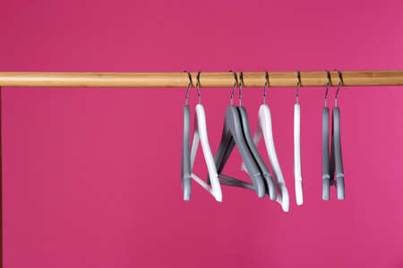 Wooden rack with clothes hangers on color background, space for text