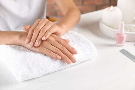 Woman showing neat manicure at table, closeup with space for text. Spa treatment
