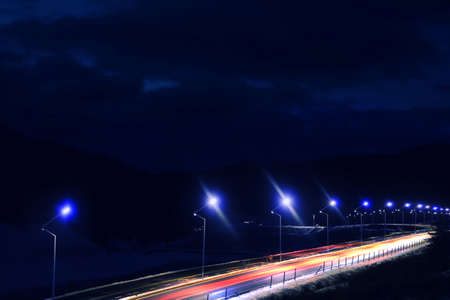 Lit mountain road on sides in evening. Design with light effects 스톡 콘텐츠 - 124655769