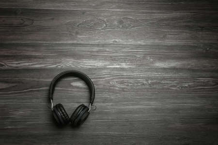 Stylish headphones on wooden background, top view. Space for text