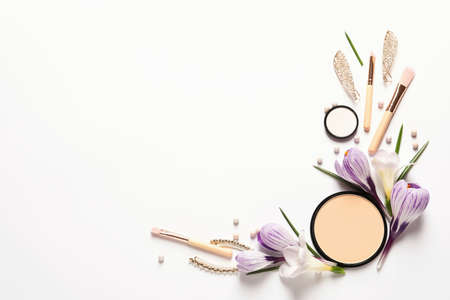 Different makeup products and flowers on white background, top view with space for text