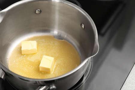 Casserole avec du beurre fondant sur une cuisinière électrique, gros plan