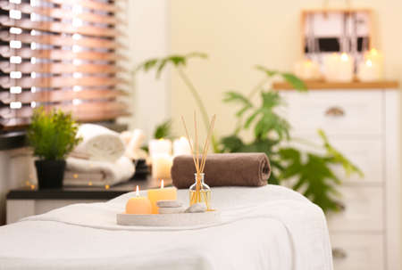 Composition with reed air freshener, candles and stones on massage table in spa salon. Space for text