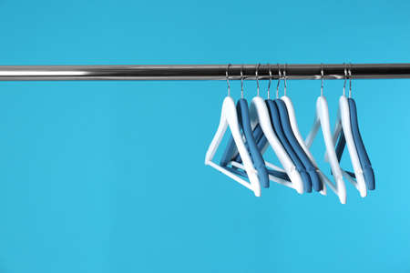 Metal rack with clothes hangers on color background, space for text 版權商用圖片