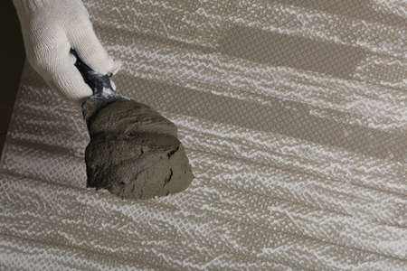 Worker holding adhesive mix on spatula above tile, closeup. Space for text 写真素材