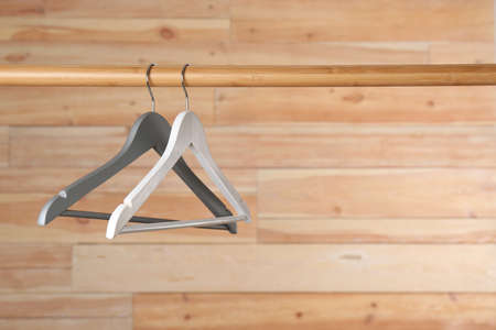 Rack with clothes hangers on wooden background, space for text 版權商用圖片
