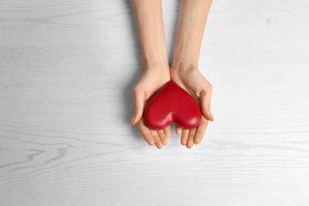 Woman holding decorative heart on white background, top view. Space for text Фото со стока