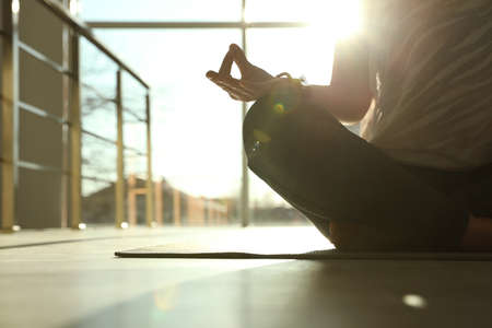 Young woman practicing yoga in sunlit room, closeup with space for text Reklamní fotografie