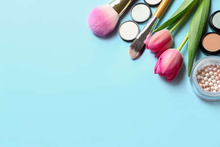 Makeup products and flowers on color background, flat lay with space for text