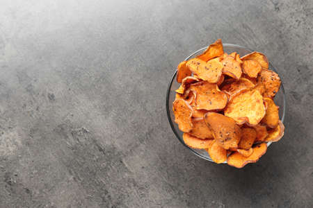 Bowl with sweet potato chips on grey table, top view. Space for text