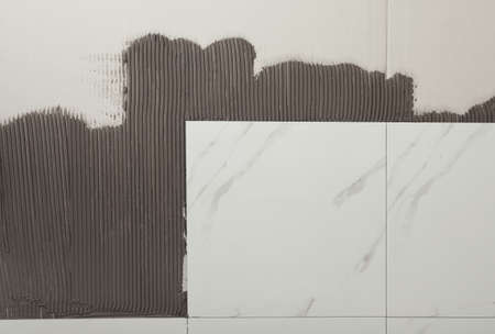 Adhesive mix and ceramic tiles on wall, top view. Space for text 写真素材