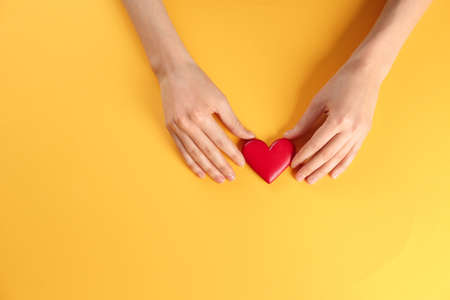 Woman holding decorative heart on color background, top view. Space for text