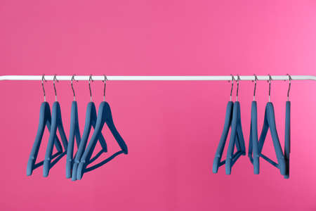 Metal rack with clothes hangers on color background
