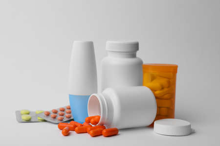 Containers and different pills on white background