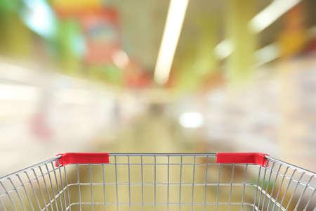 Blurred view of supermarket and empty shopping basket, closeup Reklamní fotografie