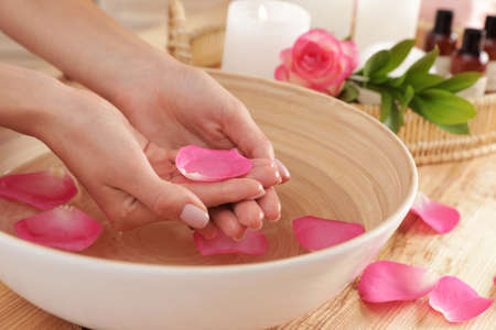 Woman soaking her hands in bowl of water and petals on table, closeup with space for text. Spa treatment