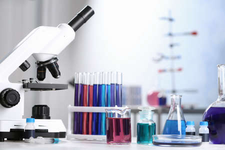 Different glassware with samples and microscope on table in chemistry laboratory