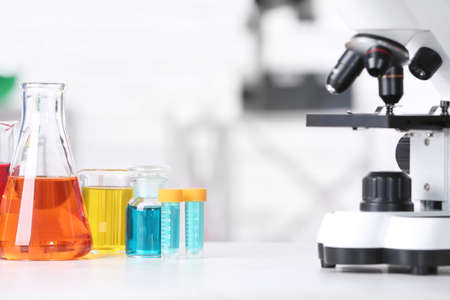 Different glassware with samples and microscope on table in chemistry laboratory Foto de archivo - 124656580