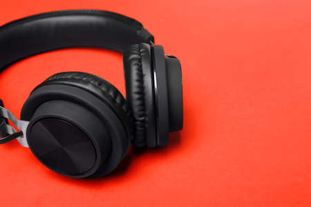 Stylish headphones on color background, closeup. Space for text